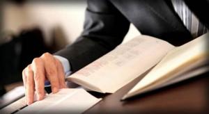 Imagen primer plano de unas manos y unos libros de un abogado especializado